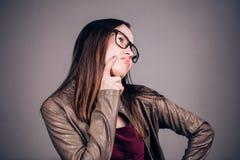 Una giovane donna nel pensiero di vetro, in dubbio, cercante, non conosce che decisione da fare immagini stock