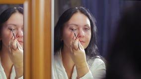 Una giovane donna nelle camice davanti ad uno specchio fa il trucco dell'occhio stock footage