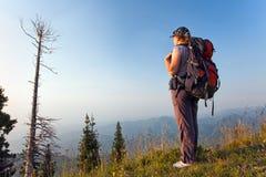 Una giovane donna nelle montagne al tramonto Fotografie Stock Libere da Diritti