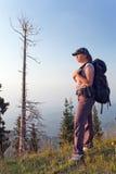 Una giovane donna nelle montagne al tramonto Immagine Stock