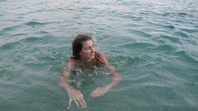 Una giovane donna nuota nel mare, filante e divertentesi esaminando la macchina fotografica video d archivio