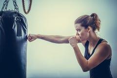 Una giovane donna pende le mani del punching ball nero Fotografia Stock Libera da Diritti