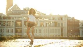 Una giovane donna in piccolo mette stare su dalla terra e realizzare in cortocircuito ballare sexy attraente sul tetto - luminoso stock footage