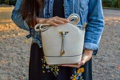 Una giovane donna, portando un vestito floreale e un rivestimento del denim, tenenti una mini borsa immagini stock