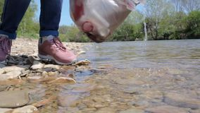 Una giovane donna raccoglie l'immondizia vicino al fiume, estrae una bottiglia dell'acqua Il concetto di miglioramento ambientale archivi video