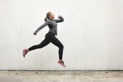 Una giovane donna, saltante in mezz'aria, all'aperto, la parete bianca dietro, minimalistic semplice, sport copre Fotografie Stock