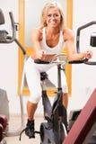 Una giovane donna sbalorditiva che per mezzo di una bici di esercizio Immagini Stock