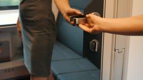 Una giovane donna sblocca ed apre una porta dello specchio con la maniglia del metallo ed entra in un compartimento comodo modern archivi video