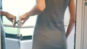 Una giovane donna sblocca ed apre una porta dello specchio con la maniglia del metallo ed esce un compartimento comodo moderno de archivi video
