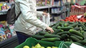 Una giovane donna sceglie e compra i cetrioli freschi in un supermercato video d archivio