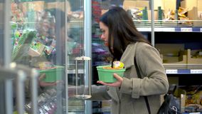 Una giovane donna sceglie e compra i prodotti lattier-caseario in un supermercato Vetrina di vetro, yogurt stock footage