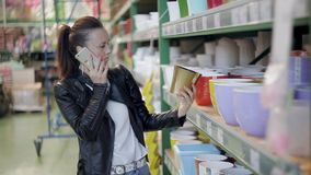 Una giovane donna sceglie e compra i vasi di plastica colorati per i fiori Negozio delle merci per i fioristi ed i giardinieri stock footage
