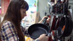 Una giovane donna sceglie una padella in un supermercato stock footage