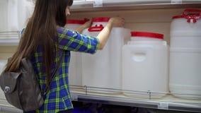 Una giovane donna sceglie un grande serbatoio di acqua nel supermercato video d archivio