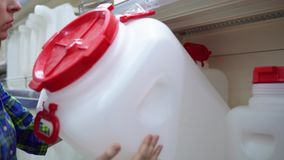 Una giovane donna sceglie un grande serbatoio di acqua nel supermercato stock footage