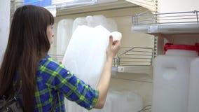 Una giovane donna sceglie un serbatoio di acqua nel supermercato stock footage