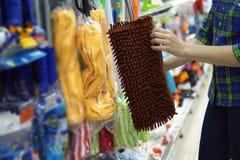 Una giovane donna sceglie una zazzera nel supermercato fotografia stock
