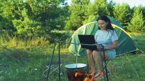 Una giovane donna si siede ad una tenda, guardante un vaso appendere sopra un fuoco e funzionare con un computer portatile archivi video