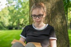 Una giovane donna si siede sotto un albero in un parco ed ha letto un libro immagini stock libere da diritti