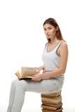 Una giovane donna si siede su una pila di libri Tiene il libro sul suo rivestimento Fotografie Stock Libere da Diritti