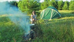 Una giovane donna si siede vicino ad un fuoco vicino alla tenda, beve il tè e guarda il giocatore di bocce appendere sopra il fuo video d archivio