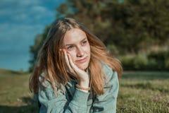 Una giovane donna si trova sull'erba ed e sembra premurosa immagini stock