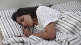 Una giovane donna si trova in un letto, la sua testa su un cuscino, lei dorme archivi video