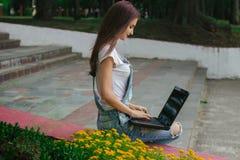 Una giovane donna snella che si siede con un computer portatile Fotografie Stock