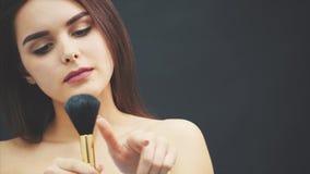 Una giovane donna spinge una spazzola con la sua mano La pelle sorvola un fondo nero Immagine potata Applicazione di trucco dentr archivi video
