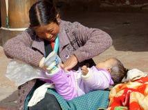 Una giovane donna sta cambiando il pannolino sui punti del tempio. Fotografie Stock Libere da Diritti
