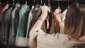 Una giovane donna sta considerando un maglione caldo, su cui un'etichetta con un prezzo pesa archivi video