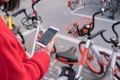 Una giovane donna sta esaminando lo Smart Phone per trovare la sua bicicletta Immagini Stock Libere da Diritti