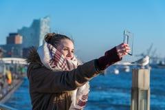 Una giovane donna sta facendo un selfie nel porto di Amburgo fotografia stock libera da diritti