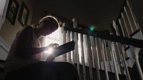 Una giovane donna sta lavorando con una compressa, sedentesi sulle scale a casa Siluetta, raggi di lustro del sole dietro stock footage
