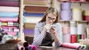 Una giovane donna sta lavorando il suoi computer portatile e telefono in un negozio di fiore donna felice del fiorista che avvolg stock footage