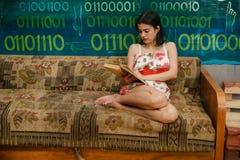 Una giovane donna sta leggendo un libro su uno strato Fotografie Stock