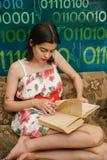 Una giovane donna sta leggendo un libro su uno strato Immagine Stock