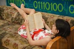 Una giovane donna sta leggendo un libro su uno strato Immagini Stock Libere da Diritti