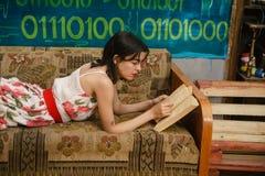 Una giovane donna sta leggendo un libro su uno strato Fotografia Stock