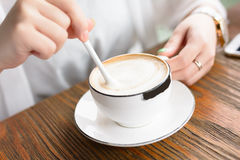 Una giovane donna sta mescolando il caffè Immagini Stock Libere da Diritti