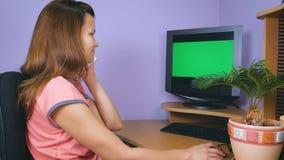 Una giovane donna sta parlando su un telefono cellulare mentre si sedeva nel suo Ministero degli Interni archivi video