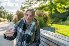 Una giovane donna sta prendendo un selfie su un banco nel parco immagine stock