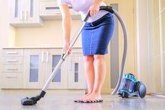 Una giovane donna sta pulendo l'appartamento Nelle mani di un elettrodomestico, aspirapolvere Il concetto di fotografia stock