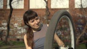 Una giovane donna sta riparando una bicicletta all'aperto video d archivio