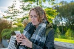 Una giovane donna sta sedendosi su un banco di parco e sta redigendo un messaggio di testo fotografia stock