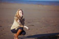 Una giovane donna sta sedendosi sulle sul suoi anche e sorridere Fotografie Stock