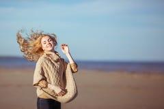 Una giovane donna sta sorridendo con i capelli che ondeggiano nel vento Fotografia Stock