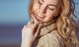 Una giovane donna sta sorridendo tenendo la sua mano sul suo collare Fotografie Stock