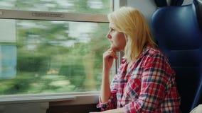 Una giovane donna sta viaggiando su un treno Sguardo fuori della finestra stock footage
