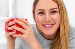 Una giovane donna sveglia sta tenendo una tazza rossa che si siede ad una tavola in un ufficio bianco Intervallo per il caffè Fotografia Stock